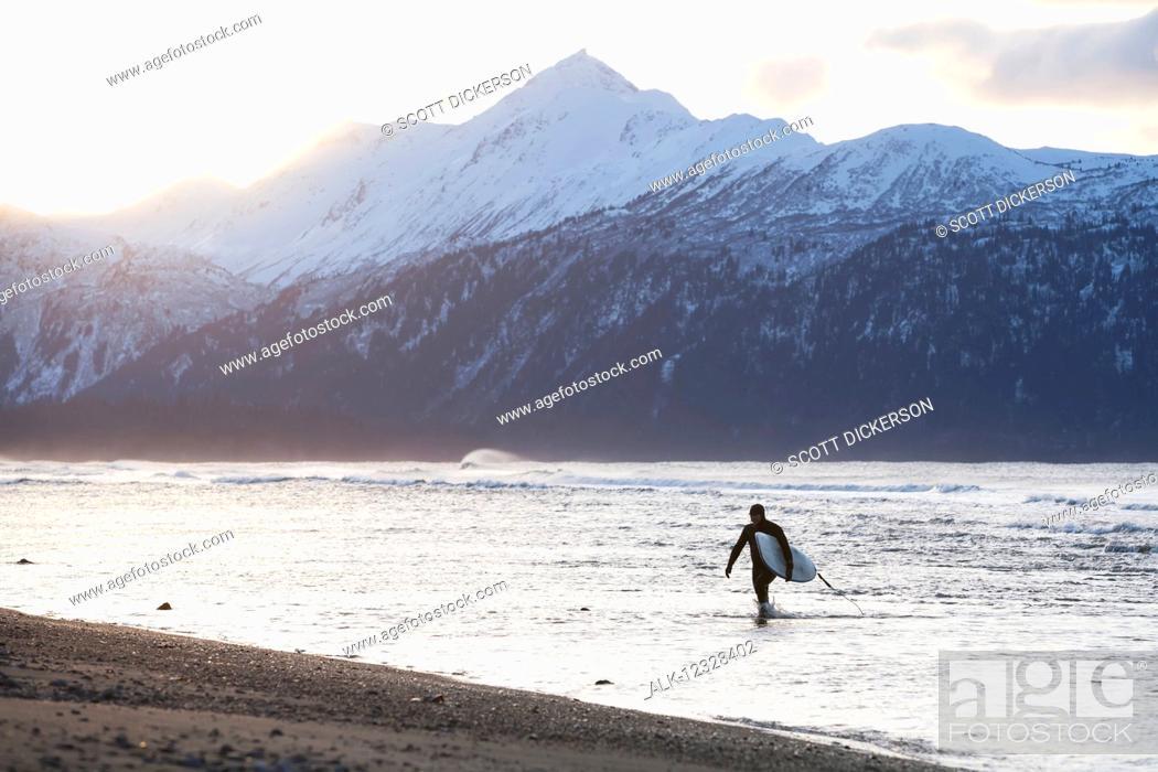 Imagen: Surfer Carries His Board Out Of Kachemak Bay, Homer Spit, Southcentral Alaska, USA.