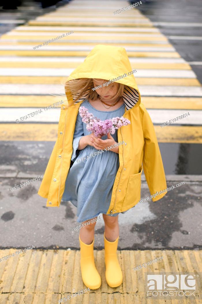 Stock Photo: Girl wearing yellow rainjacket, standing on zebra crossing, holding lilac.