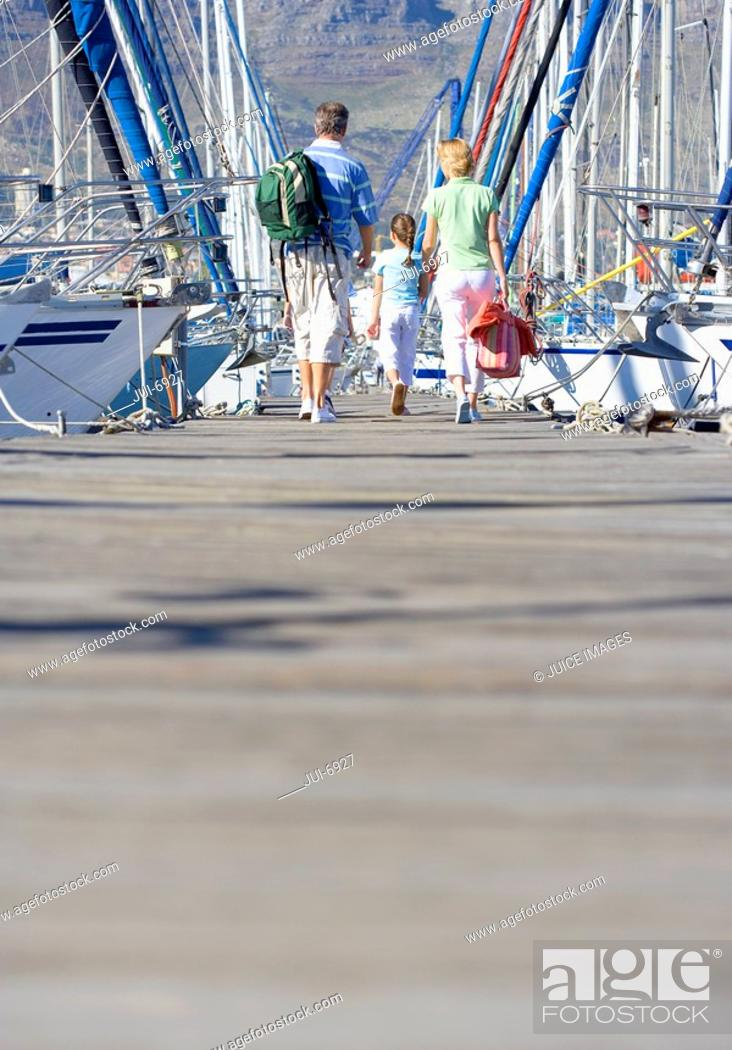 Stock Photo: Family walking side by side in mid-distance along harbour jetty, rear view.