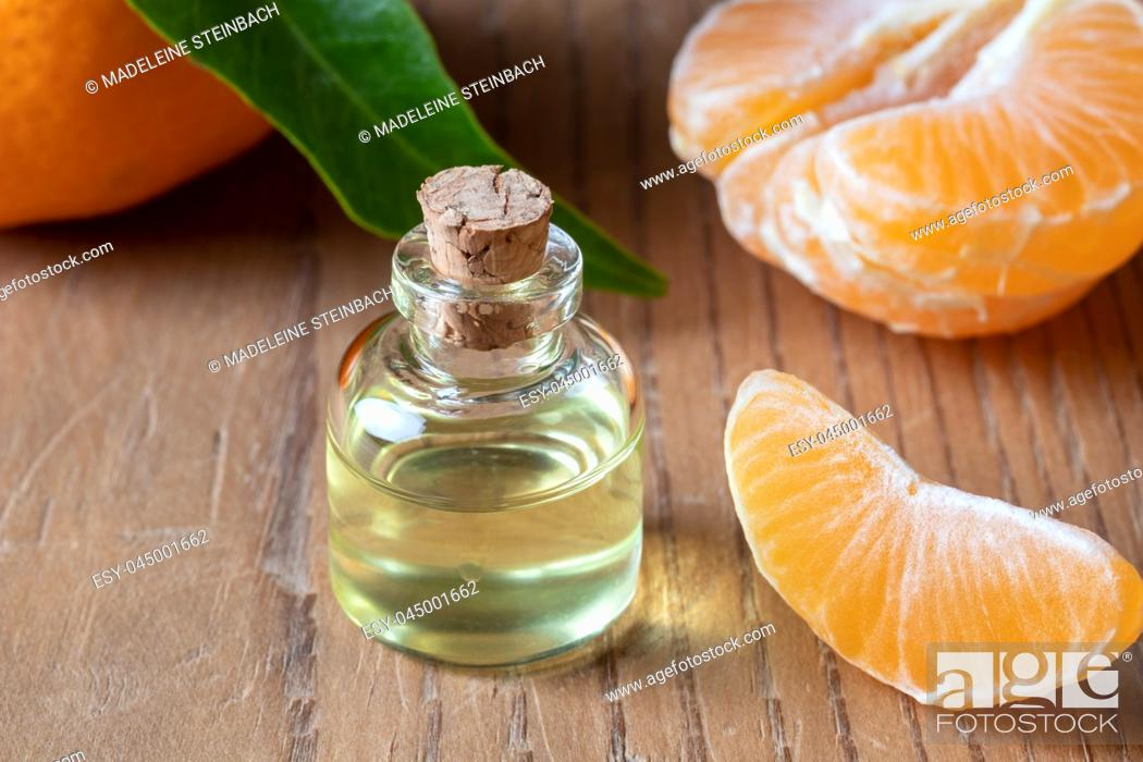Stock Photo: A bottle of essential oil with fresh tangerines.