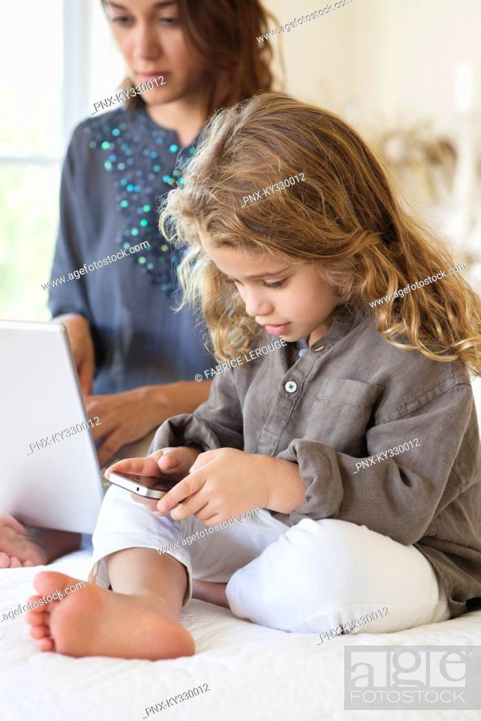 Stock Photo: Girl looking at a smart phone with her mother working on a laptop on the bed.