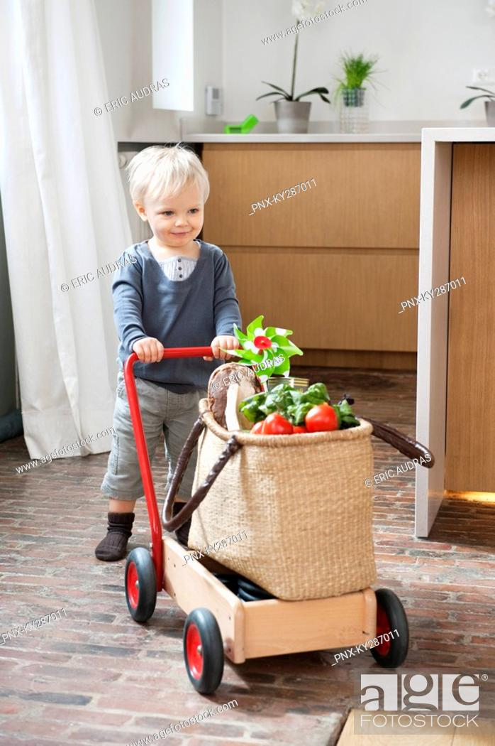 Stock Photo: Boy pushing a cart with a vegetable bag on it.