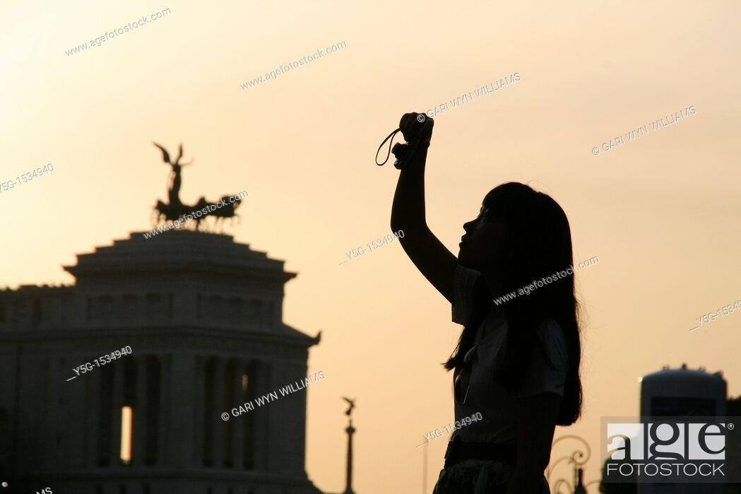 Stock Photo: woman taking photograph on via dei fori imperiali street in rome italy.