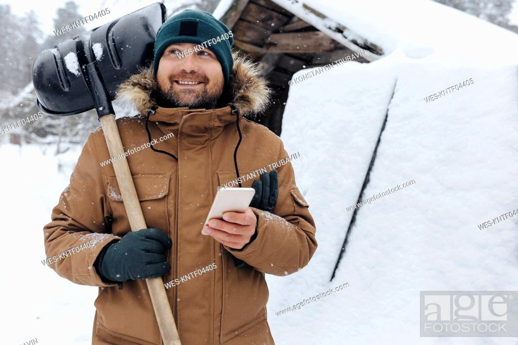 Photo de stock: Portrait of smiling man with snow shovel and cell phone.