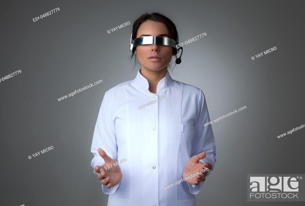 Stock Photo: Female scientist or doctor using futuristic VR goggles headset with microphone and holding virtual object.