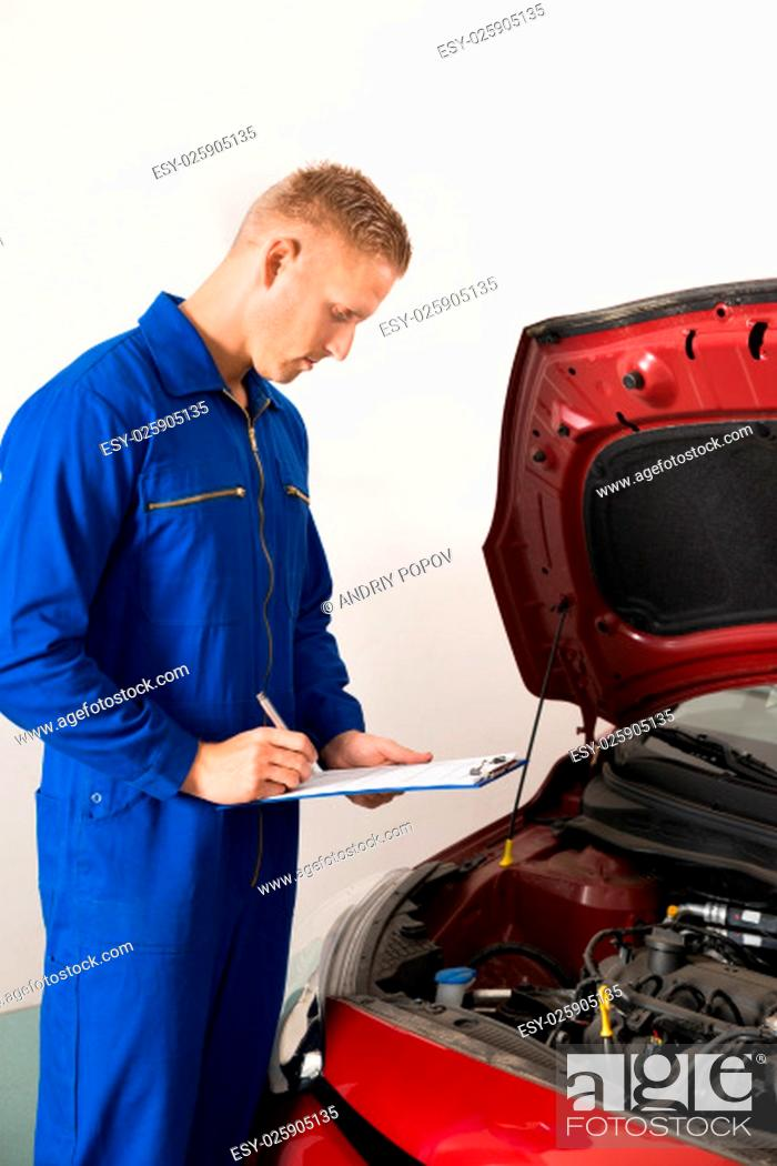Stock Photo: Mechanic Standing Near Car Writing On Clipboard In Garage.