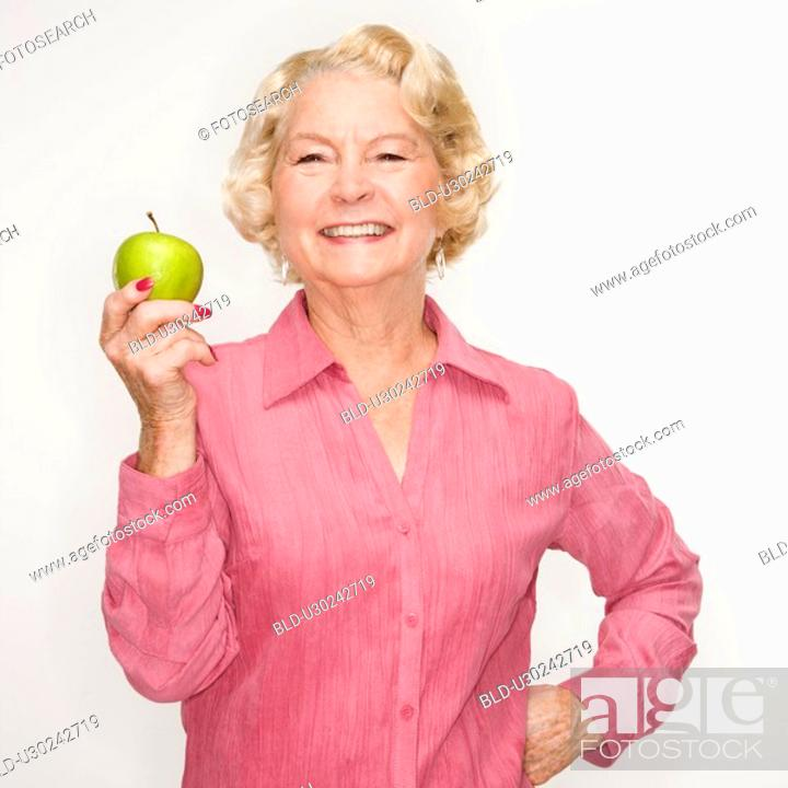 Stock Photo: Caucasian senior woman holding apple smiling at viewer.