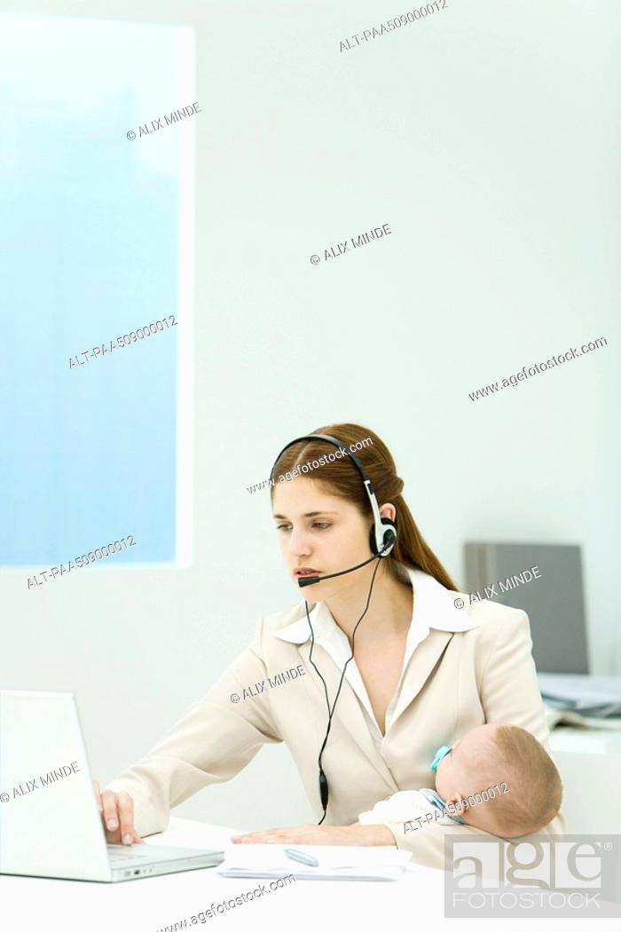 Stock Photo: Professional woman in office, holding baby, using headset and laptop computer.