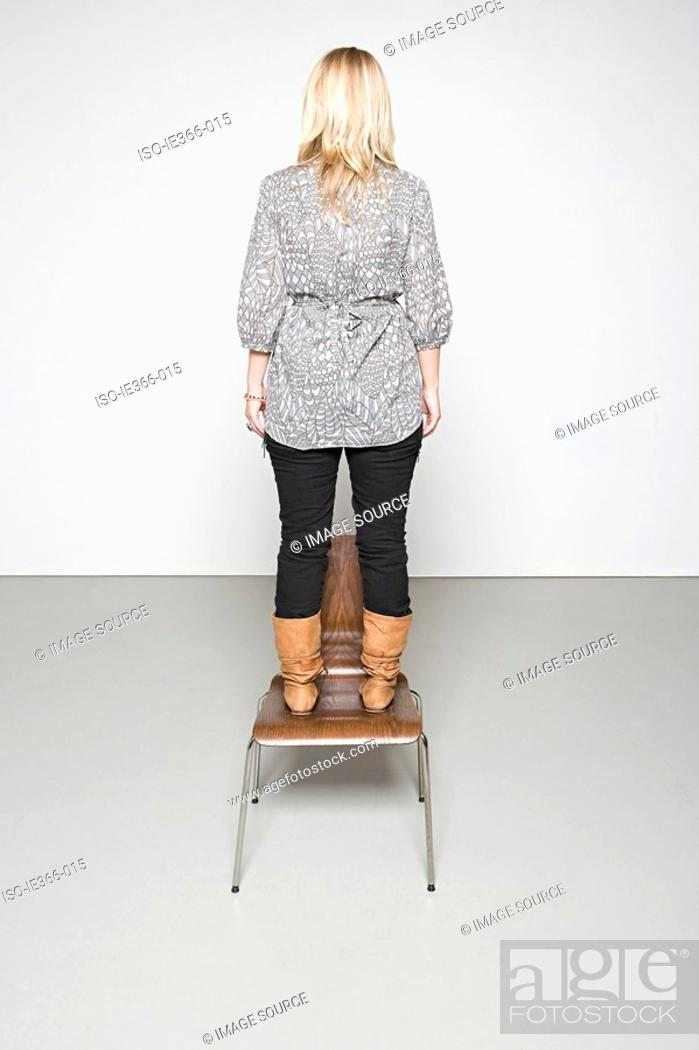 Stock Photo: Woman standing on a chair.