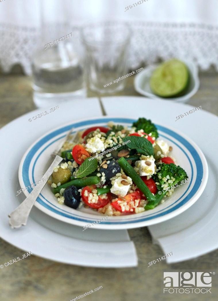 Stock Photo: Greek salad with green beans, broccoli, tomatoes, bulgur and olives.