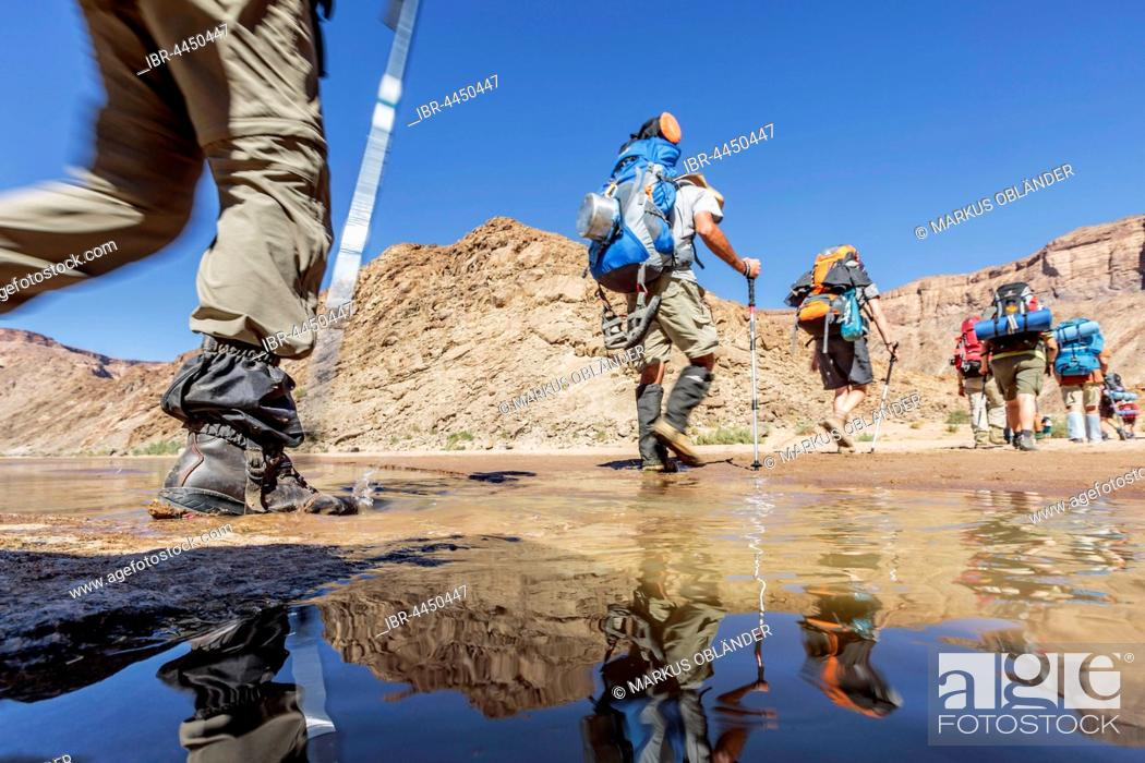 Stock Photo: Hikers with backpacks crossing Fish River, Fish River Canyon, Namibia.