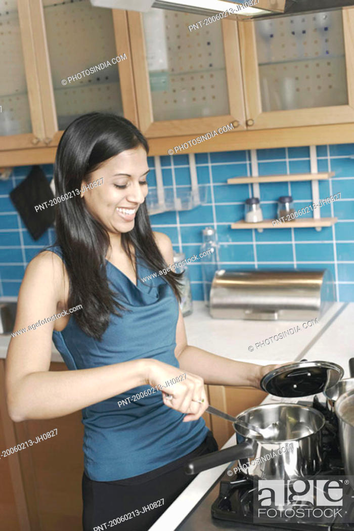 Stock Photo: Young woman cooking in the kitchen.