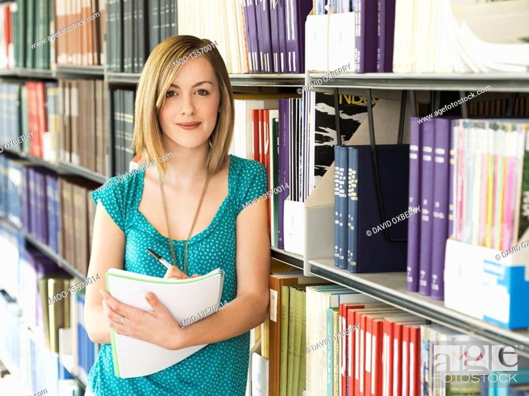 Stock Photo: Young woman standing by bookshelf in library taking notes.