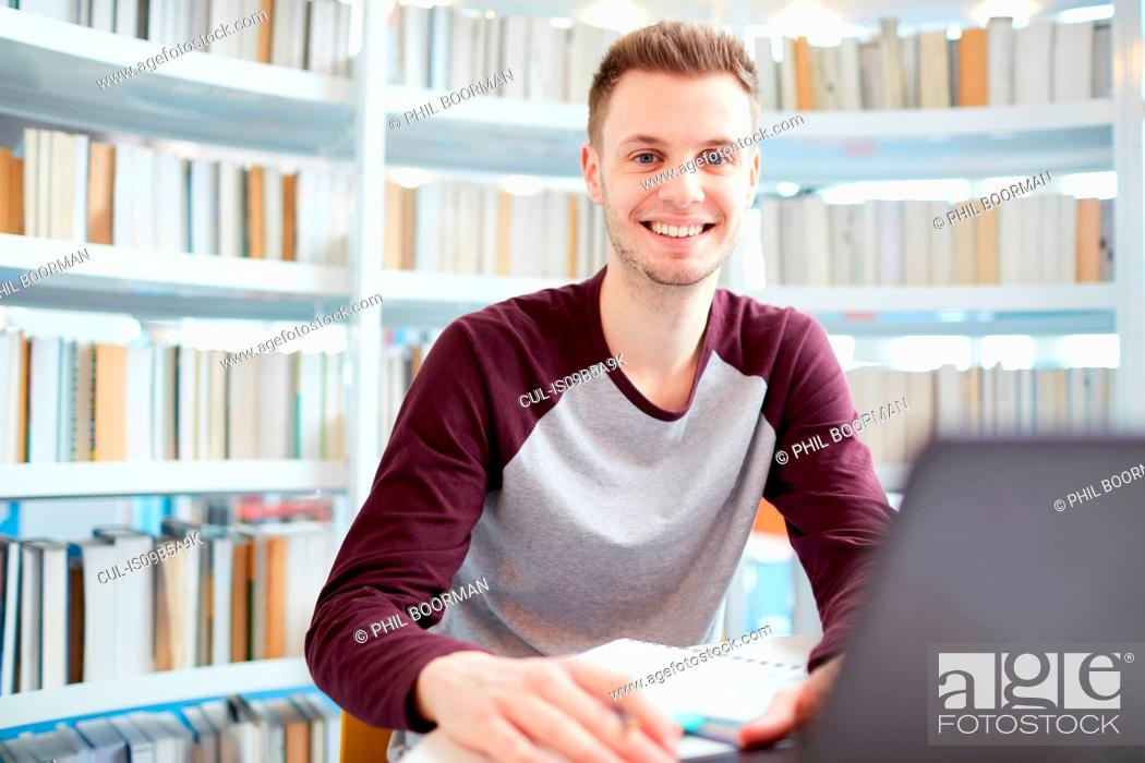 Stock Photo: University student working in library.