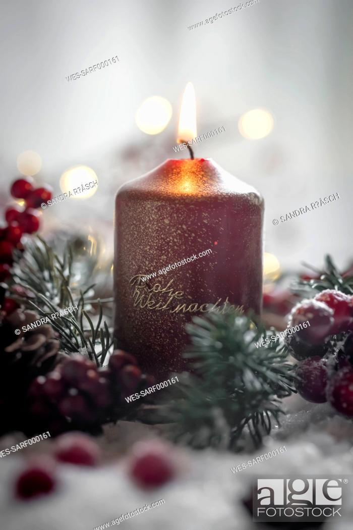 Stock Photo: Lighted Christmas candle, fir branch and artificial snow.