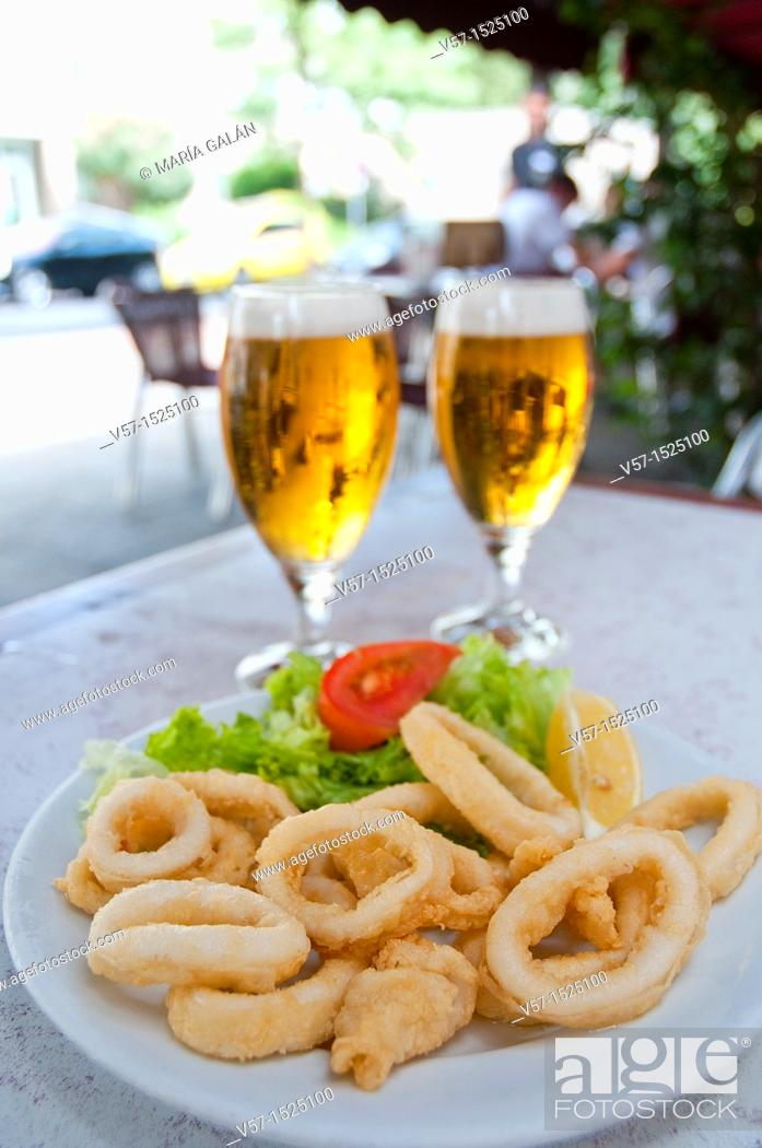 Stock Photo: Fried squids serving and two glasses of beer in a terrace. Madrid, Spain.
