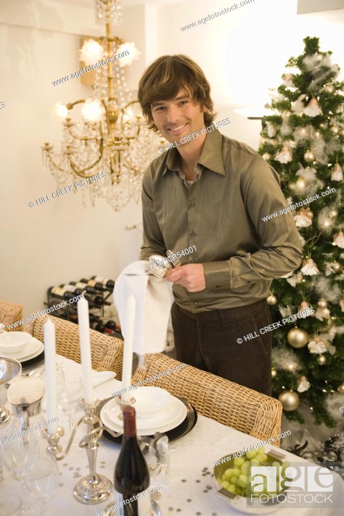 Stock Photo: Man setting ornate dinner table.