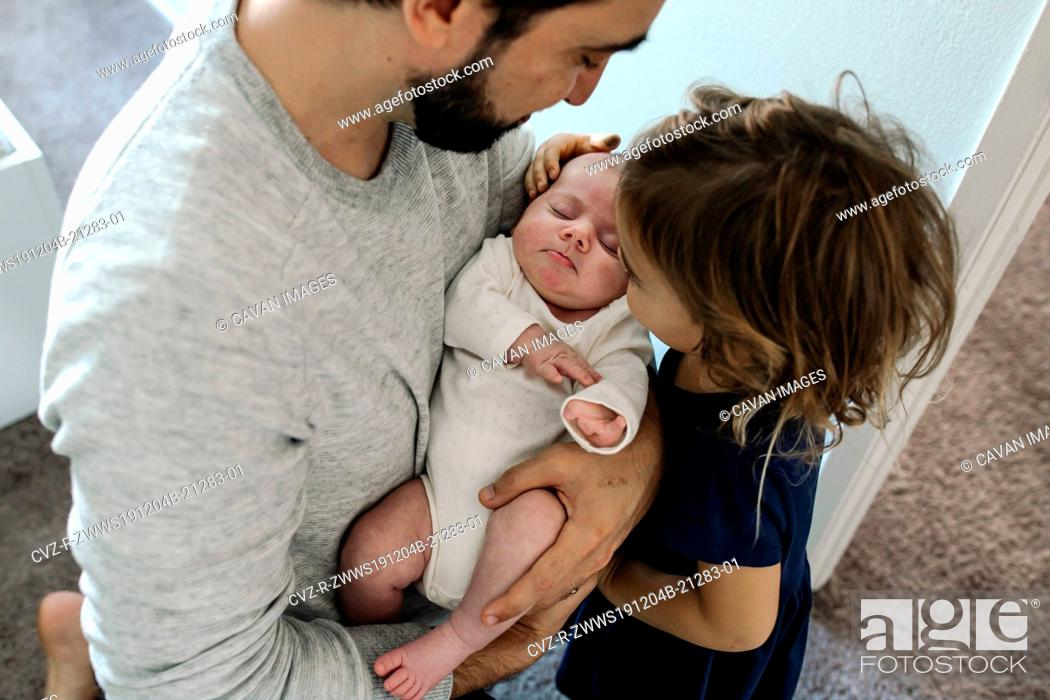 Stock Photo: Big sister touching head of newborn held by dad with beard.