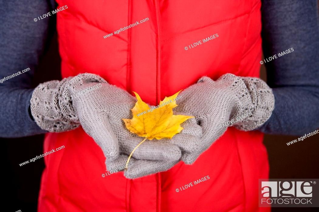 Stock Photo: A woman holding an autumn leaf.