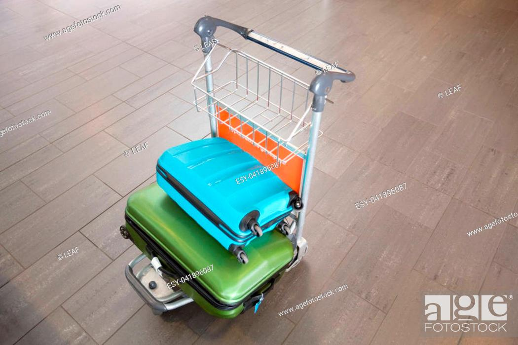 Stock Photo: High angle view of green and blue luggage in trolley at airport.