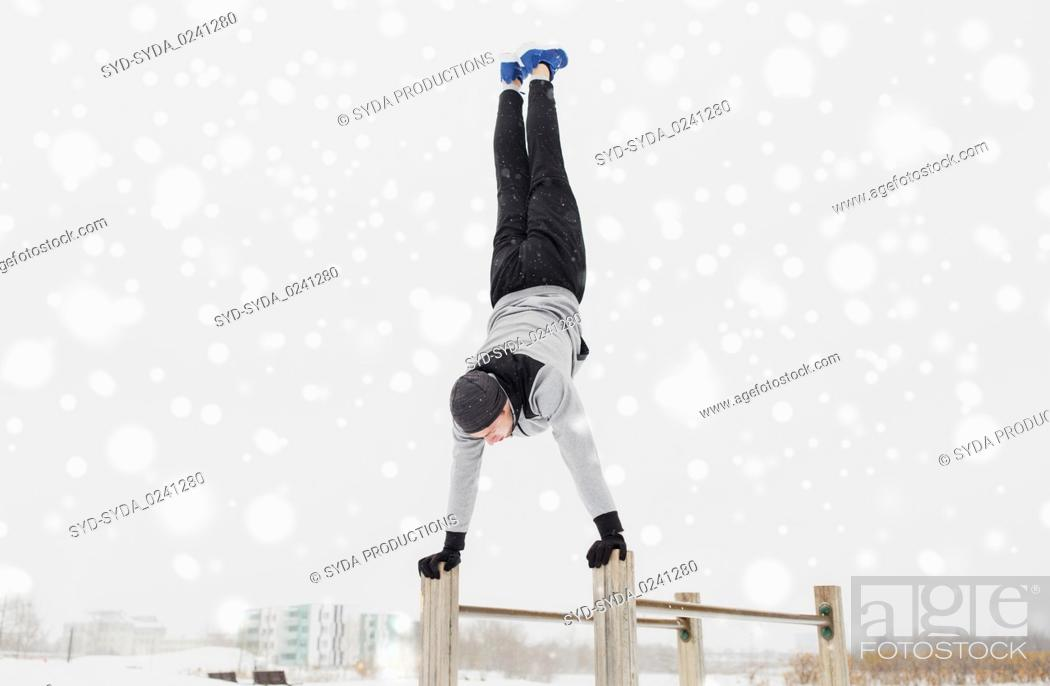 Stock Photo: young man exercising on parallel bars in winter.