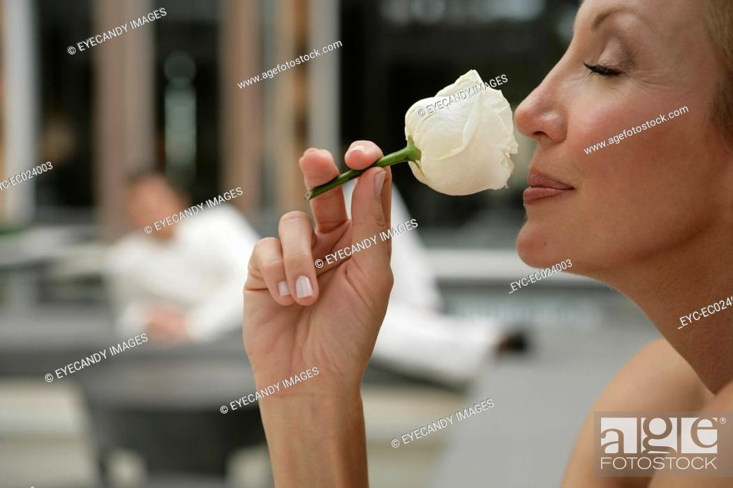 Stock Photo: View of a woman smelling a rose.