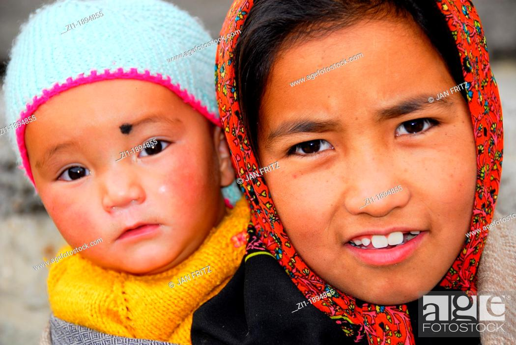 Photo de stock: portrait of child carrying younger sister at the back.