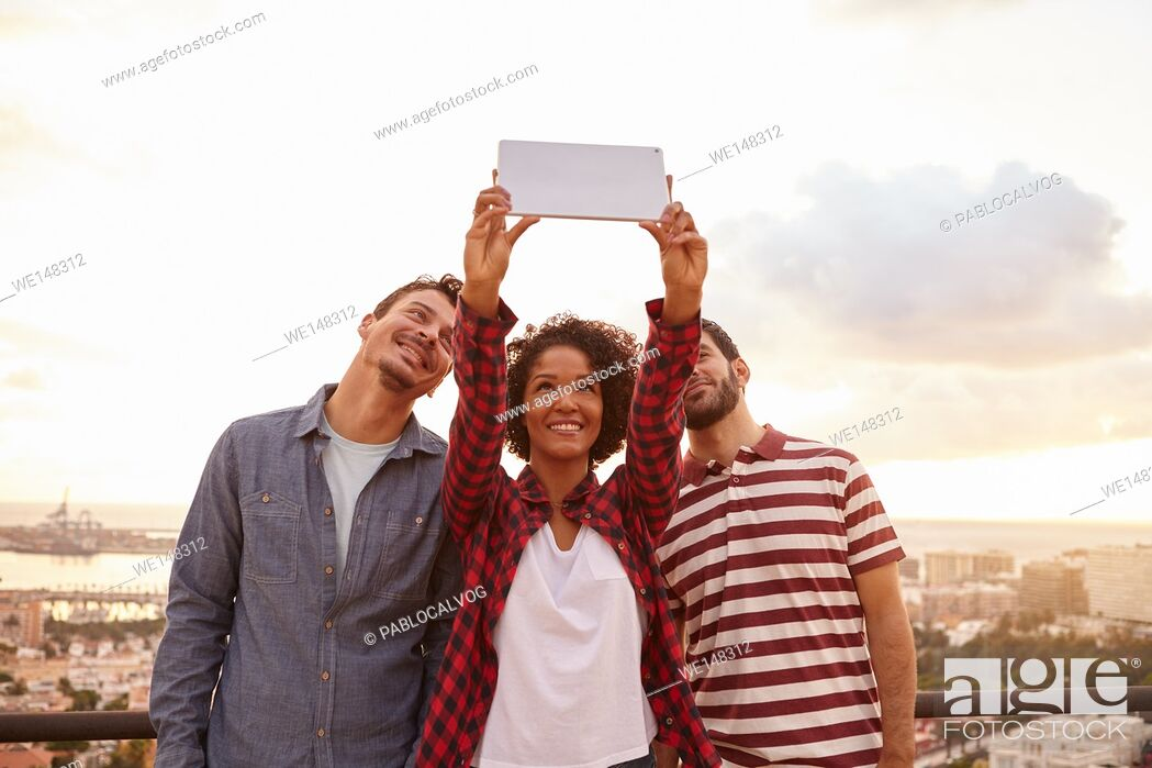 Stock Photo: Three good friends taking a selfie on a tablet while standing on a bridge overlooking a city, wearing casual clothing.