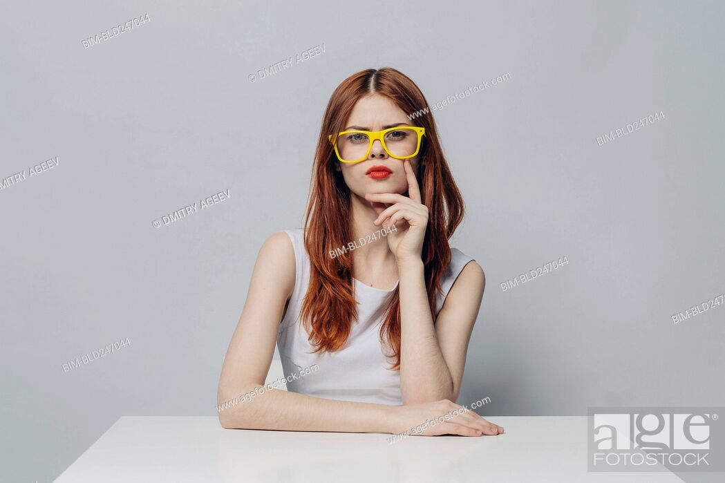 Stock Photo: Serious Caucasian woman sitting at table wearing yellow eyeglasses.