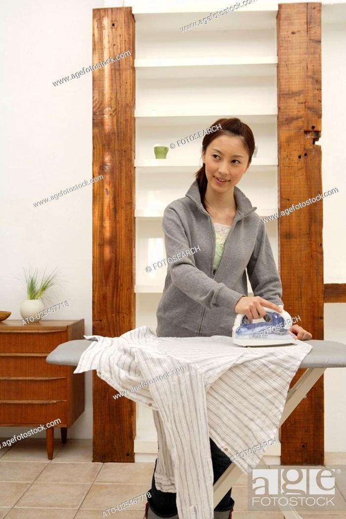 Imagen: View of a young woman ironing a shirt.