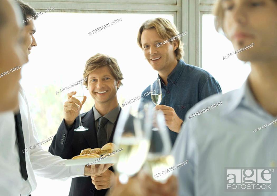 Stock Photo: Two male executives raising glasses of champagne during office party.