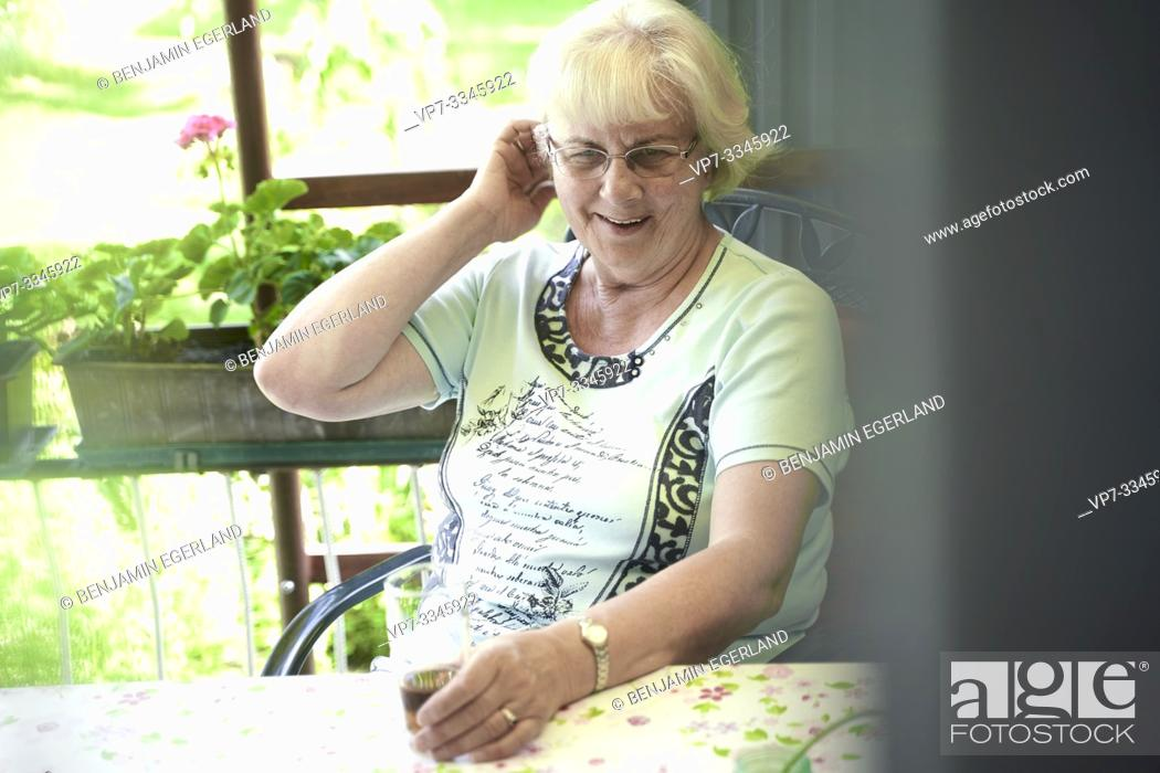 Stock Photo: senior woman sitting at table outdoors in allotment garden.