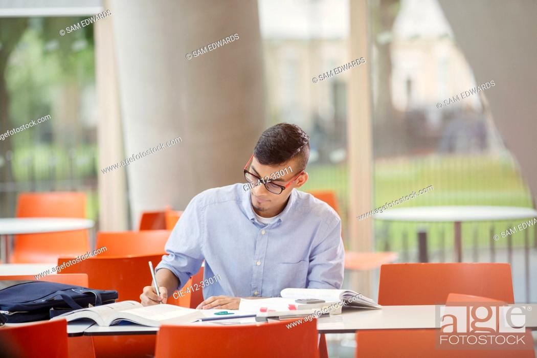 Stock Photo: Male college student studying at table.