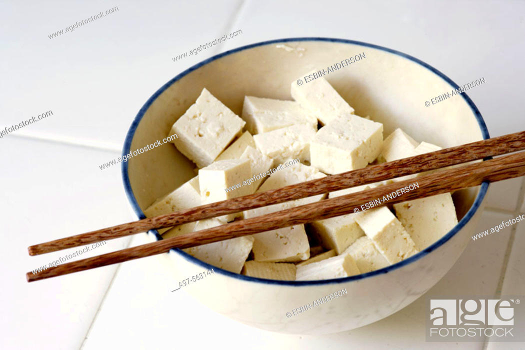 Stock Photo: Pieces of Tofu cut into cubes and sitting in a bowl with a pair of chopsticks resting on top.