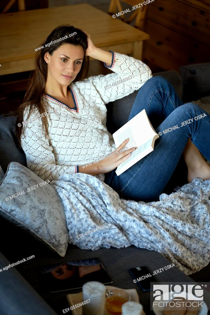 Stock Photo: beautiful young brunette woman reading a book on a gray sofa.