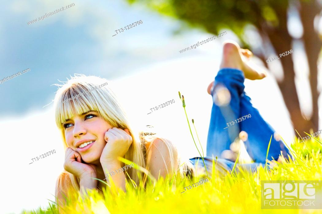 Stock Photo: Enjoying sun teen girl is lying on the grass.