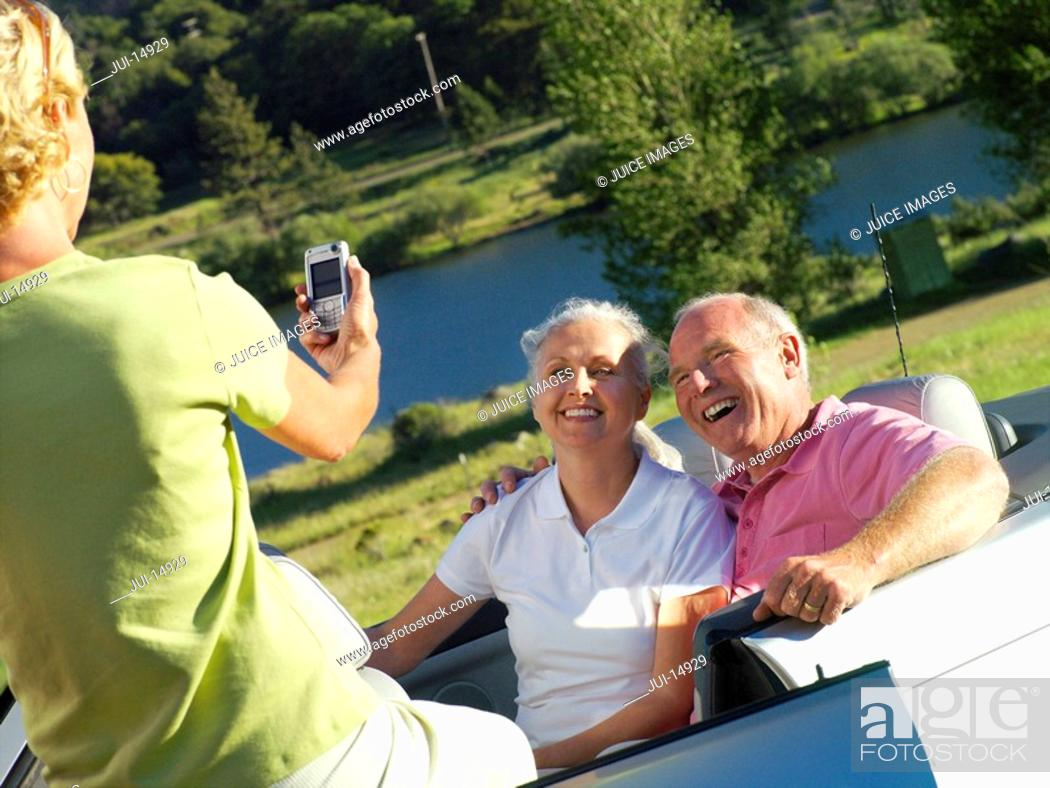 Stock Photo: Woman taking photograph of senior couple by river.