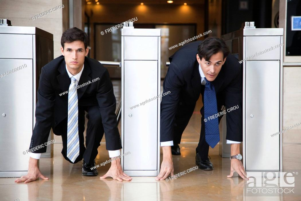 Stock Photo: Businessmen crouching in starting position in lobby turnstiles.
