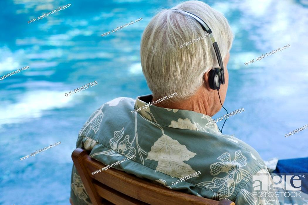 Stock Photo: Man wearing headphones sitting by a pool.