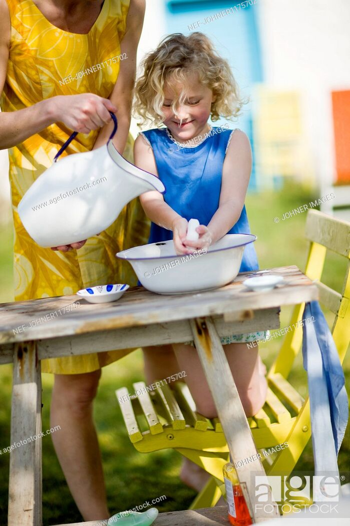 Stock Photo: Mother and daughter washing hands in backyard.