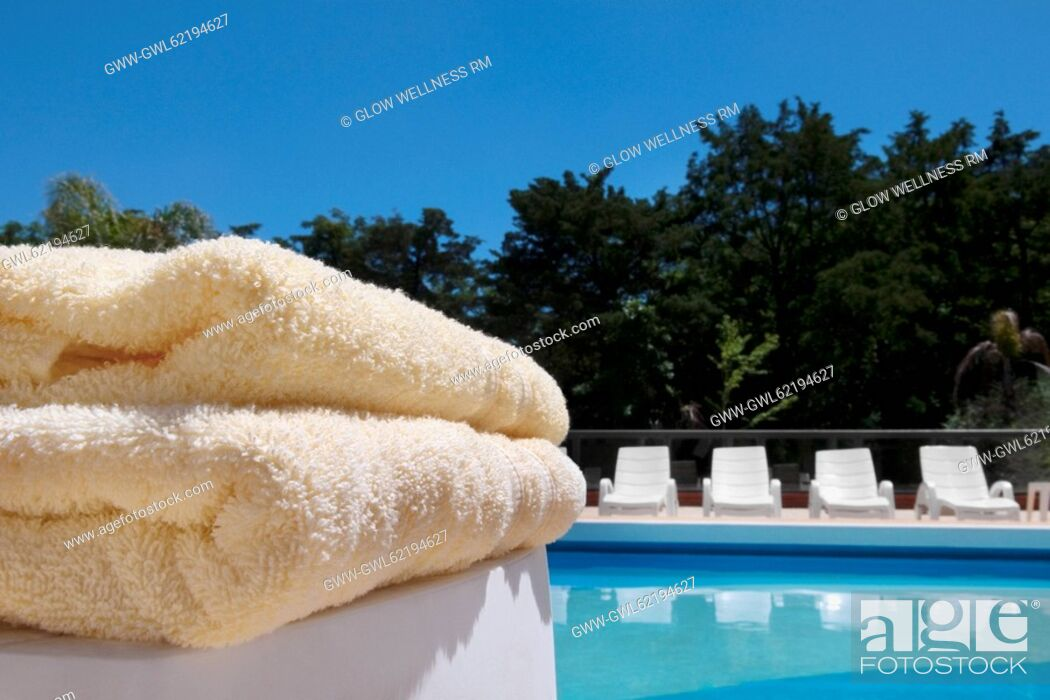 Imagen: Close-up of towels and lounge chairs at the poolside.