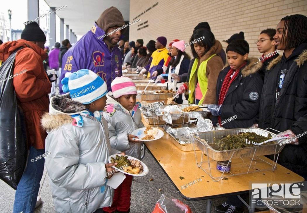 Stock Photo: Washington, DC - Volunteers serve food to the hungry at an outdoor soup kitchen  The volunteer project was one of many Martin Luther King Day community service.