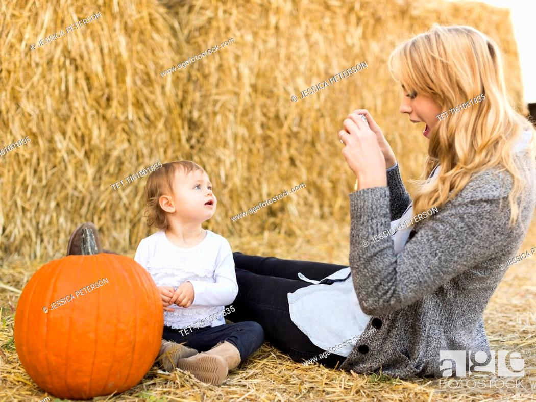 Stock Photo: Mother photographing daughter (12-17 months) with large pumpkin.