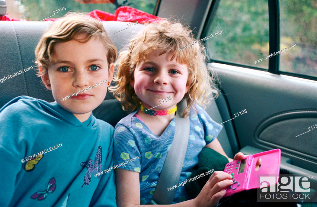 Stock Photo: Two sisters as passengers in a car on a family outing.