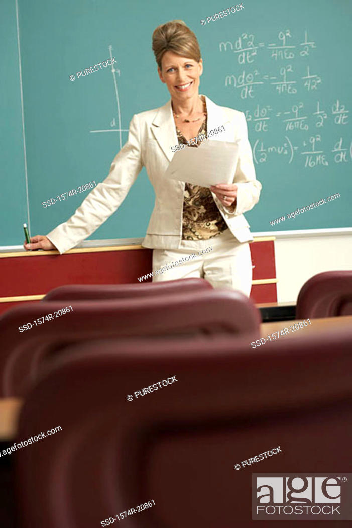 Stock Photo: Portrait of a professor standing in front of a blackboard and holding a paper.