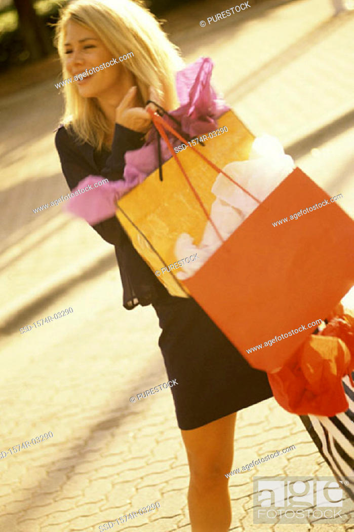 Stock Photo: Young woman standing with shopping bags.