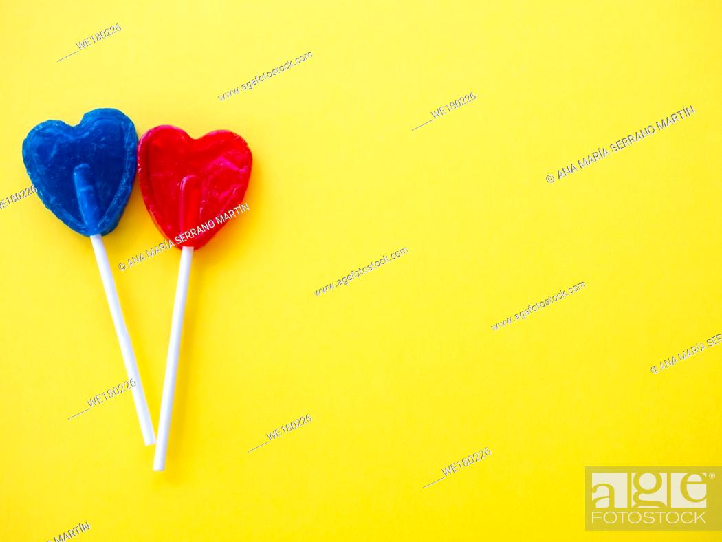 Stock Photo: Blue and red lollipop on a yellow background.