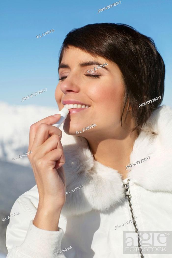 Stock Photo: Young woman applying lip balm.