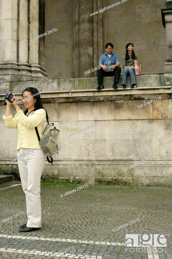 Stock Photo: Asian woman with a camera standing in front of two sitting people.