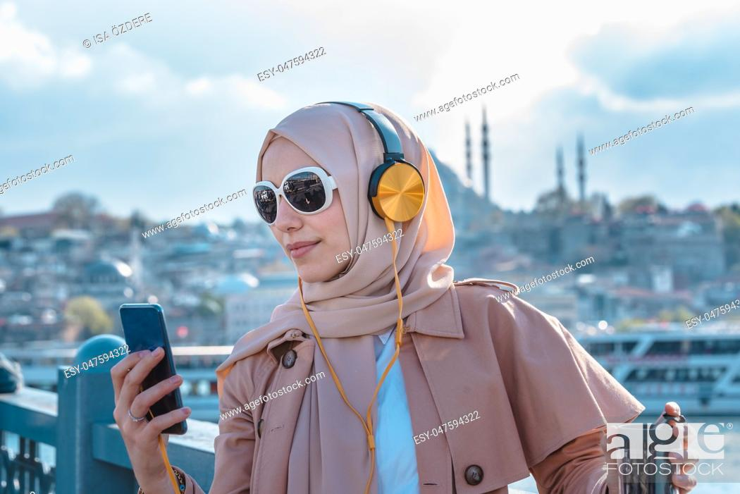 Stock Photo: Beautiful Muslim woman in headscarf and fashionable modern trendy clothes with headphones,smartphone and sunglasses takes selfie with mosque view.